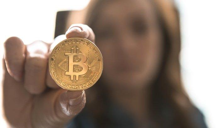 žena držící bitcoinovou minci